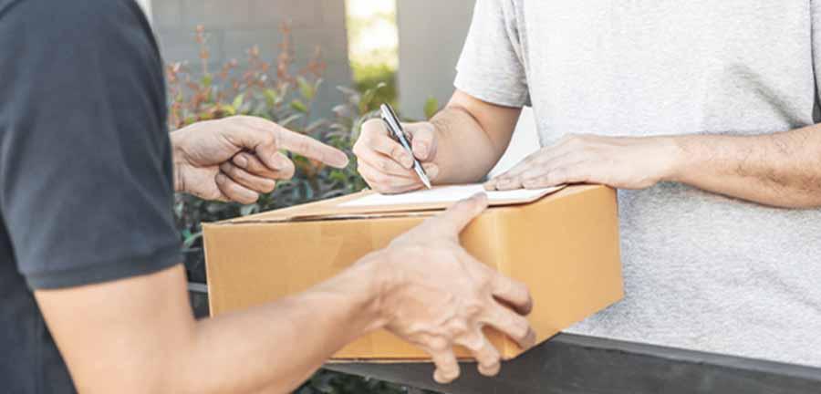 Kurier przekazujący paczkę klientowi - YourHomeStory Wyposażenie wnętrz